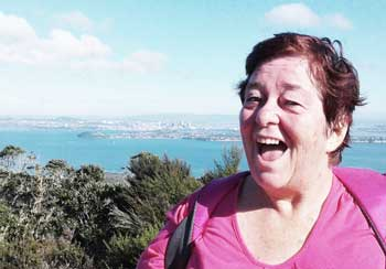 Helen smiling with view of Auckland harbour in the background.