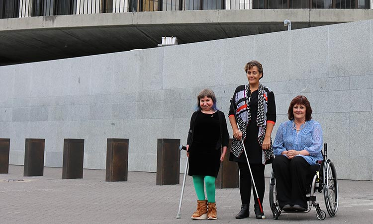 Three women with disabilities standing in front of the Beehive.