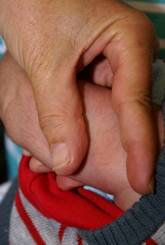Image of an infant's arm and a health care worker's hand.