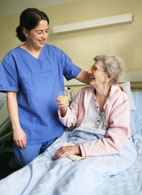 Nurse standing beside patient who is in bed.
