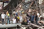 Photo of a group of men in the rubble of a collapsed building, pointing and looking at something away from the building.