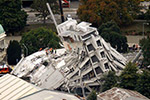 Photo of a building that has almost completely collapsed. A group of workers are standing on the roof of the building.