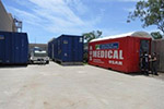 Photo of several shipping containers, one which says 'AUS MEDICAL USAR'.