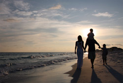 Photo of a family on the beach, walking towards the rising sun.