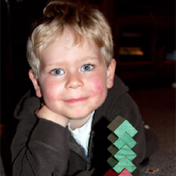 Photo of a smiling toddler next to his block tower.