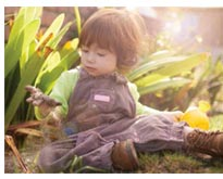 image of child playing in garden with dirt
