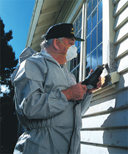 Photo of a man removing paint from a window frame.