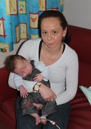 Photo of Jenah holding an exhausted-looking Nixson in her lap.