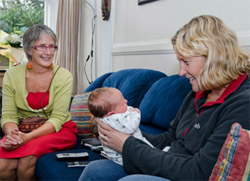 Photo of a woman sitting on her couch with her new baby on her lap. Her Lead Maternity Carer looks on.
