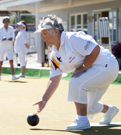 A grey-haired Māori woman plays bowls with a determined look on her face.