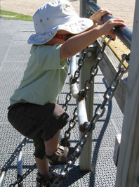 Photo of a toddler climbing on a playground.