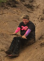 Photo of Izzy's mum sliding down a muddy slope.