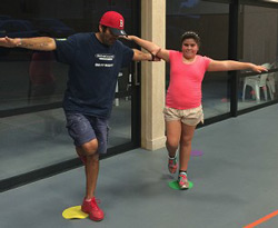 Photo of Izzy and her dad doing balance exercises.