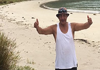 Photo of Matua Paul on the beach, giving two thumbs up.