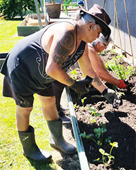 Photo of Michael Houhia helping out in the garden.