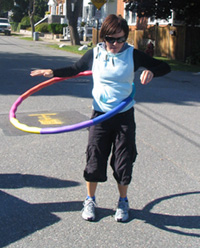 Photo of a young woman hula-hooping.