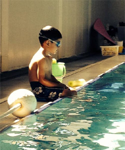 Photo of a young boy sitting at the side of the pool with his goggles on.