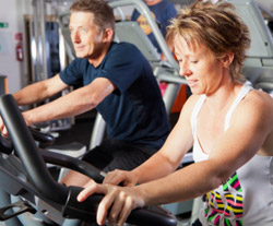 A middle-aged man and woman on the stationary bikes at a gym.