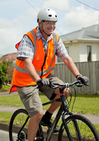 A man cycling down the street wearing a bright orange reflector vest, a helmet and cycling gloves.