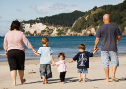 A family walking down a beach holding hands, with the littlest child breaking the chain because she's turned to face the camera.