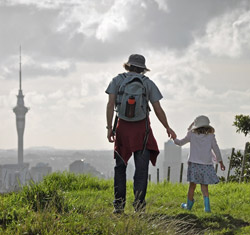 A father and daughter walk over a field holding hands, with the Sky Tower in the distance.