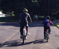 Photo of a father and son cycling down a suburban street.