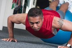 A man doing push-ups, with his legs raised up on a fitness ball.