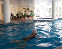 An older woman swimming in an indoor pool.