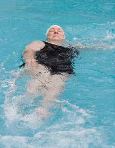 An older woman doing the backstroke.
