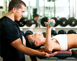 A woman lying on her back and lifting weights, with her personal trainer spotting her.