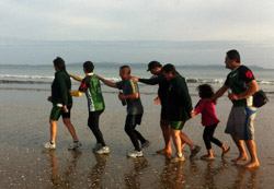 Photo of a whānau walking along the beach, pretending to do a conga line.