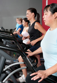 A row of women running or walking on treadmills.