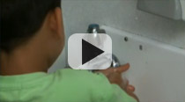 Video link: image showing a young boy washing his hands.