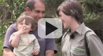 Link to video, showing a young woman in a Department of Conservation uniform, standing with a man holding a toddler.